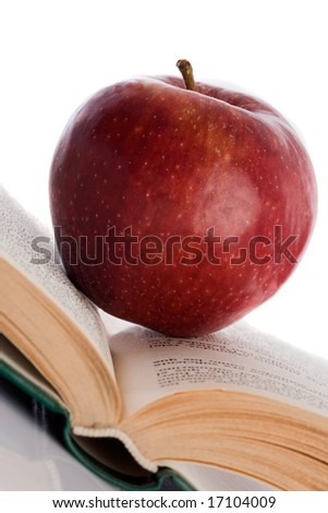 Apple red on open book inclined to reflect on the floor