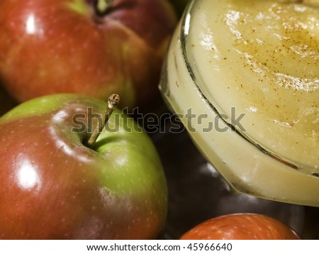 apple sauce dessert (stewed apple) with whole apples around. Shallow depth of field.