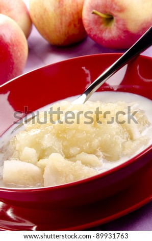 Apple sauce with fresh milk in a red bowl