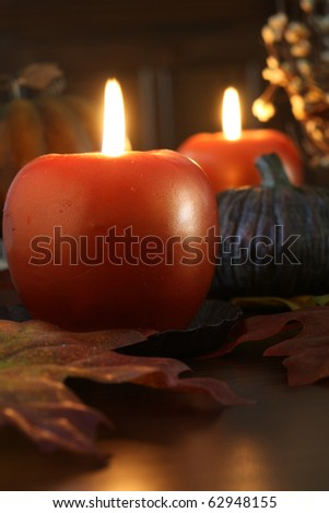 Apple shaped candles surrounded by autumn decorations. Also available in horizontal.