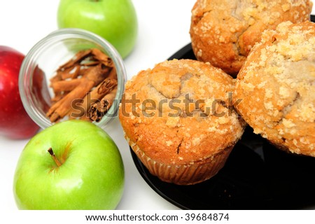 Apple Spice muffins on a white background with 2 green granny smith, one red apple and cinnamon sticks