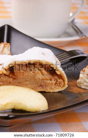 Apple strudel (Apfelstrudel) served on a black plate with a tea cup in the background. Selective focus, shallow DOF.