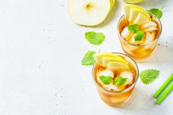 Apple summer refreshing ice mocktail, apple iced tea in glasses. Space for text, top view.