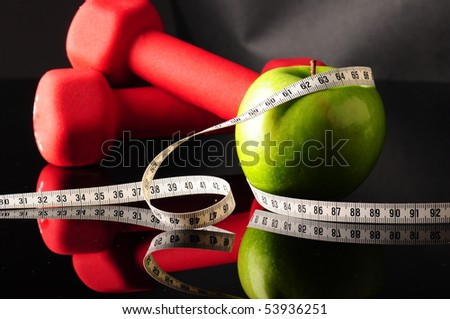 apple, tapeline and dumbbells