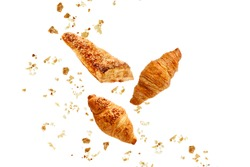 Apple turnover, french butter and almond nut croissants flying with crumbs isolated on white background.