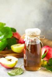 Apple vinegar. Healthy organic food. A bottle of apple cider vinegar on a light stone countertop. Copy space.