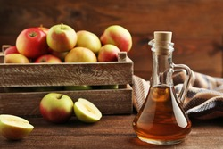 Apple vinegar in glass bottle on brown wooden table