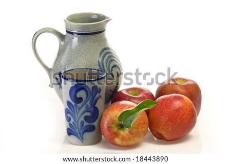 Apple wine in a jug with beaker and apples on bright background