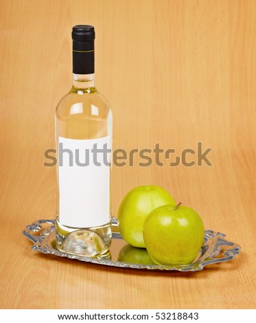 Apple wine in the closed bottle on a metal tray