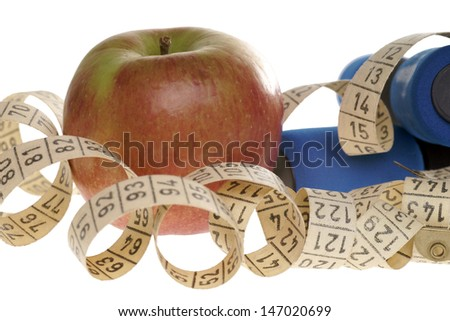 Apple with measure tape and dumbbells / healthy living