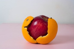 Apple with orange skin. Transformation concept with fruit. Deceptive appearance of food. Fresh produce is not always how it appears.