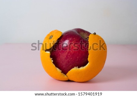 Apple with orange skin. Transformation concept with fruit. Deceptive appearance of food. Fresh produce is not always how it appears.  Stock foto ©