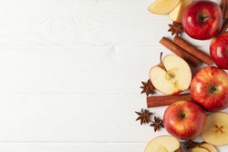 Apples and cinnamon on wooden background, space for text