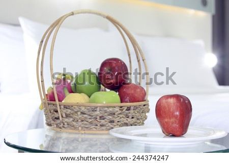 Apples and group of fruit present for breakfast in the bedroom.