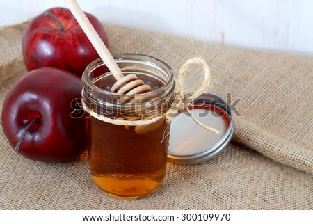 Apples and honey are representative of the concept of hoping for sweetness in the coming year during the Jewish New Year holiday of Rosh Hashanah. Includes a honey dipper and twine on a burlap surface Stockfoto ©