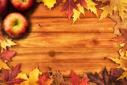 Apples and maple leaves disposed on a wooden table. Flat lay, top view of autumn decoration concept.