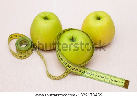 Apples and measuring tape on the table. Diet, proper nutrition #1329173456
