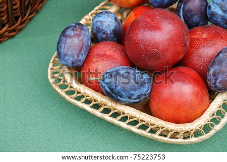 Apples and plums crop in a basket