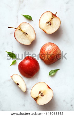 Apples flat lay on a marble background. Group of sliced and whole apple fruits viewed from above. Top view #648068362