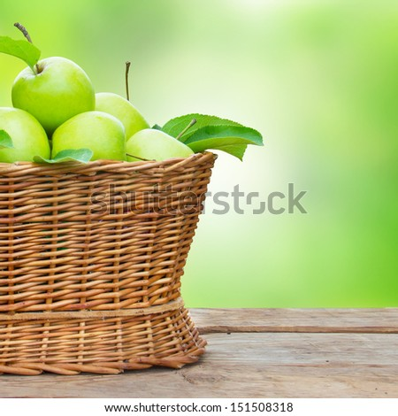 apples in a basket on wooden table against garden background