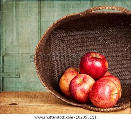 Apples in basket on grunge background, vintage or antique look