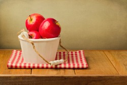 Apples in wooden bucket on tablecloth over vintage background