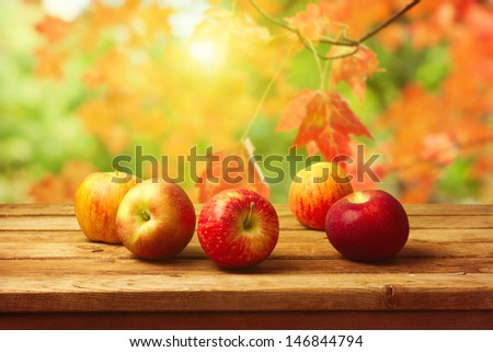 Apples on wooden table over autumn bokeh background