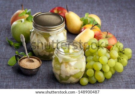 apples pears grapes in a sugar syrup in the pot with sugar and mint