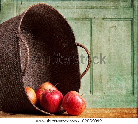 Apples spilling out of a basket on grunge background, vintage or antique look