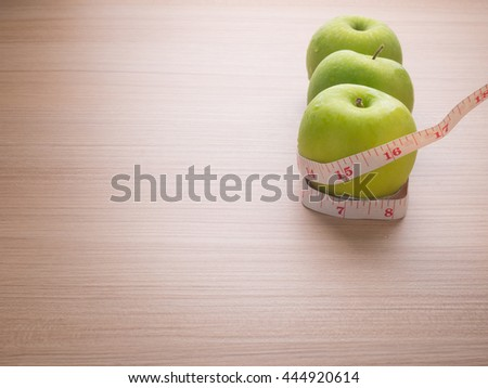 Apples with tape measure on brown wood background, lose weight concept #444920614