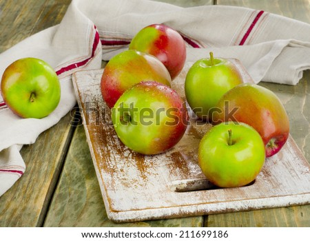 Apples with water drops on a wooden table.