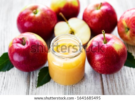 Applesauce in glass jar and fresh apples on a wooden table stock photo