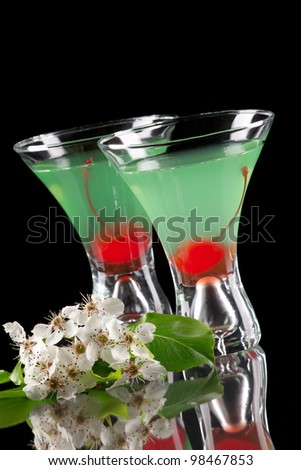 Appletini cocktail in contemporary martini glass over black background garnished with maraschino cherry, and apple blossom. Most popular cocktails series.