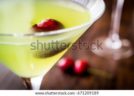 Appletini Cocktail with cherry on wooden surface.  #671209189