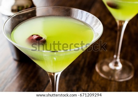 Appletini Cocktail with cherry on wooden surface.  #671209294
