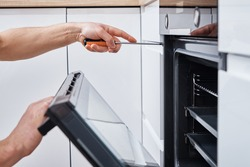 Appliance repair. Man installing electricity oven in the kitchen