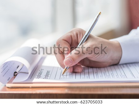 Applicant filling in company application form document applying for job, or registering claim for health insurance #623705033