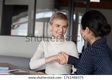 Applicant successfully pass job interview got hired international company position feels happy shake hands HR indian ethnicity manager. Client and insurer make deal handshaking express regard concept