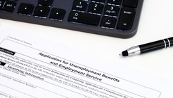 Application for employment benefits form with computer keyboard and pen on white background. Unemployment rate has risen sharply in United States due to closed business caused by corona virus outbreak
