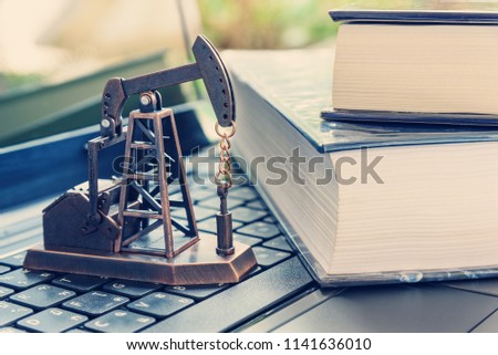 Applied petrochemical research and study concept : Oil rig or pump jack, two thick textbook on a laptop computer, depicts the activities related to production of hydrocabons, crude oil or natural gas Photo stock ©