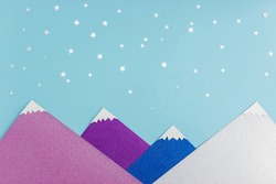 Applique made of colored paper and silver confetti on a blue background. Starry sky and snow-capped peaks of the mountains. Sweet night concept.