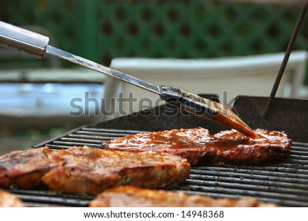 Applying BBQ Sauce to Steak on a Grill