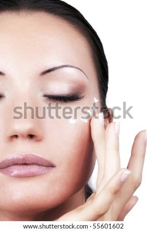 Applying cream for eyes area, portrait closeup