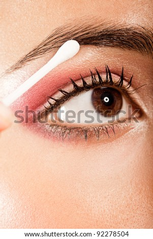 Applying Eye Makeup Eye Open. Woman with brown eyes using a cotton bud to blend her eye makeup, closeup on eye.