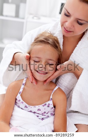 Applying face cream after bath - little girl and woman having fun - stock photo