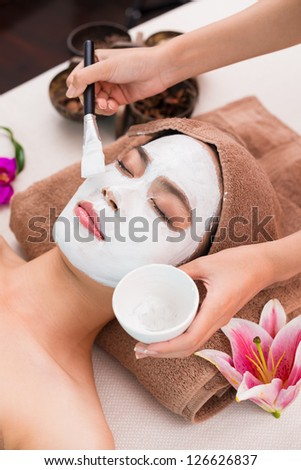 Applying facial mask on a female face