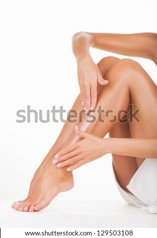 Applying moisturizer cream on the legs  isolated on white background