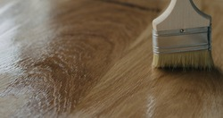 applying oil finish to oak surface with brush