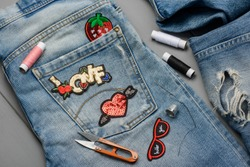 Applying patches to denim. Embroidered and sequin decorative elements to embellish worn jeans. DIY project concept.