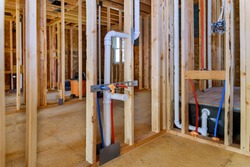 Applying pipe drain plumbing with hot red and cold blue pex pipe inside a house bathroom frame
